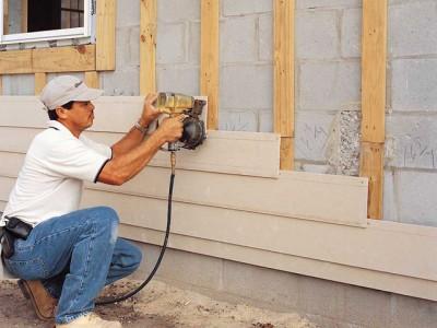 Процесс монтажа панелей сайдинга на стену дома