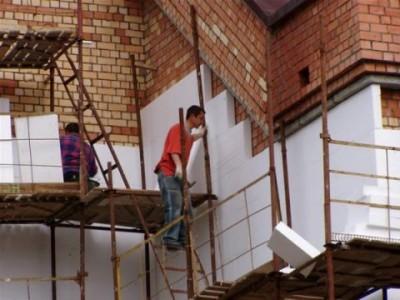 Процесс монтажа утеплителя на стену дома