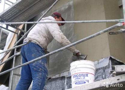Процесс нанесения штукатурки на фасад дома