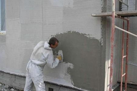 Процесс нанесения штукатурки на стену дома