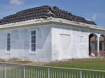 Обработанный грунтовкой дом перед финишной отделкой